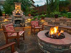 Backyard landscaping stone work with stone fire place and chairs
