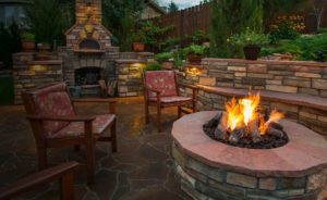 Backyard landscaping with stone fireplace and chairs