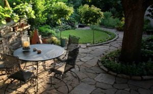 Backyard landscaping stone in trees with table and chairs